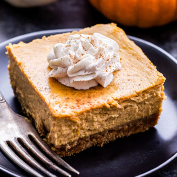Creamy Pumpkin Pie Bar on a black plate with a fork.