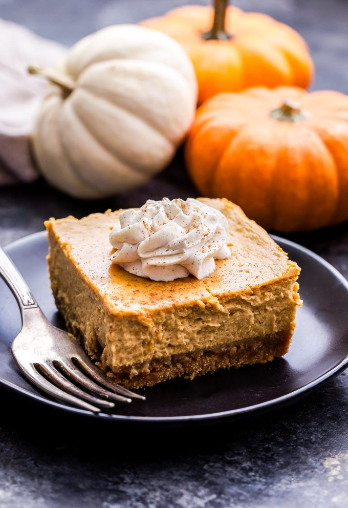 Creamy Pumpkin Pie Bars topped with whipped cream on a black plate with a fork on it. Mini pumpkins in the background.