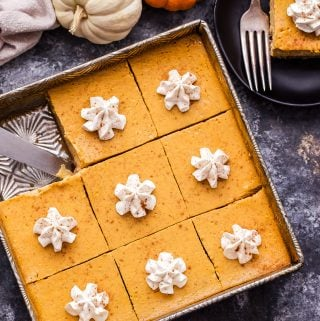 Overhead photo of Creamy Pumpkin Pie Bars in a metal baking pan with a bar cut out. Bar is on a black plate in the background.