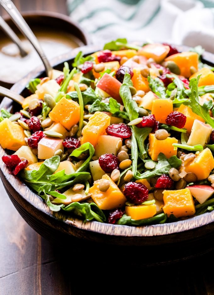 Butternut Squash Lentil Salad with cranberries, arugula, pepitas, apples in a wooden bowl with spoons in the salad bowl and a small bowl of vinaigrette behind the salad.