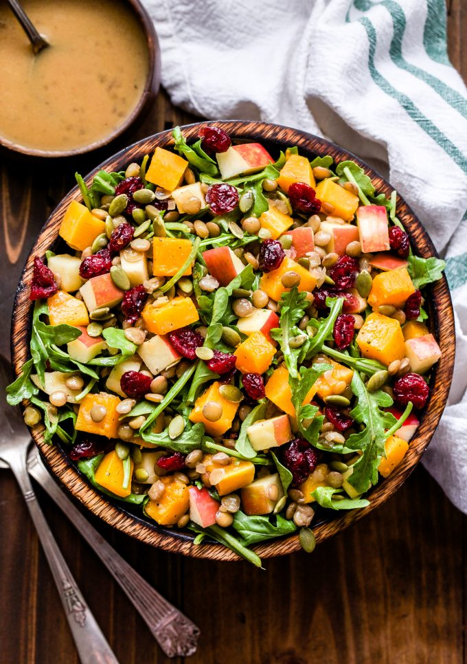 Butternut Squash Lentil Salad with cranberries, arugula, pepitas, apples in a wooden bowl. Serving spoons and a small bowl of cider vinaigrette next to the salad bowl.