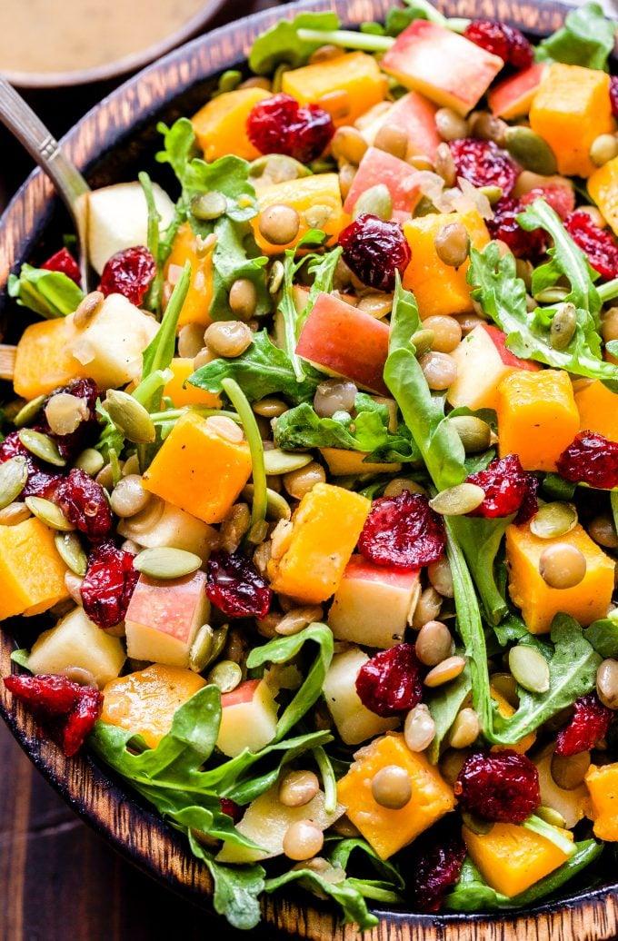 Butternut Squash Lentil Salad with cranberries, arugula, pepitas, apples in a wooden bowl.