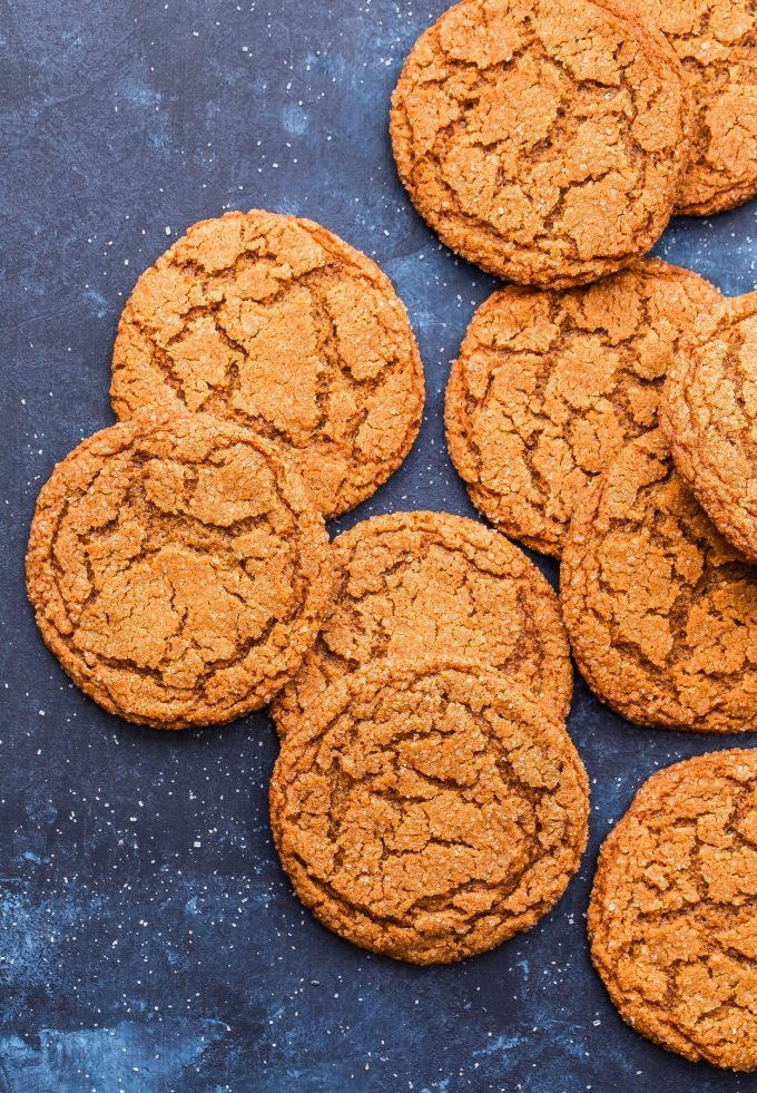 Chewy Ginger Molasses Cookies scattered on blue background.