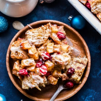 Cranberry Apple French Toast Casserole drizzled with vanilla glaze on a wood plate with a fork. Maple syrup in the background.
