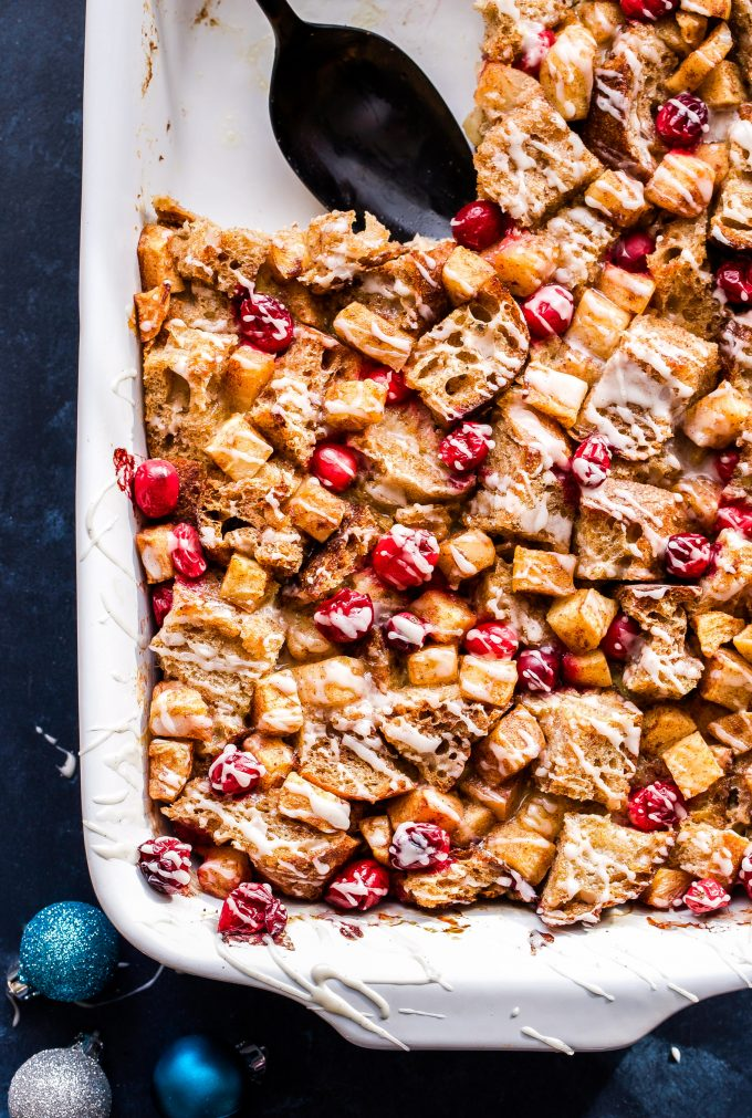 Cranberry Apple French Toast Casserole in a white baking dish with a piece scooped out.