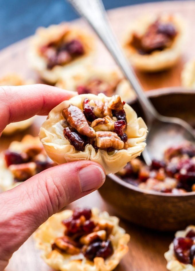 Hand holding one of the Cranberry Maple Pecan Baked Brie Bites