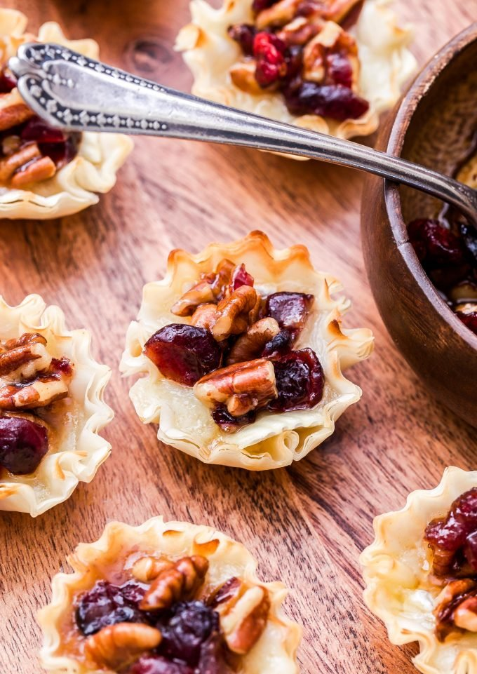 closeup photo of Cranberry Maple Pecan Baked Brie Bites next to a wooden bowl and spoon with the cranberry pecan topping in it.