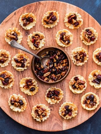 Cranberry Maple Pecan Baked Brie Bites on a round wooden serving platter with a bowl of the cranberry pecan topping in the middle.