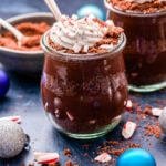 Peppermint Chocolate Pudding Parfaits topped with coconut whipped cream and crushed candy canes in jars with spoons in them.