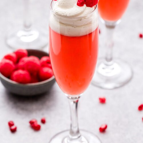 Pomegranate Raspberry Rosé Jello Cups in champagne flute topped with whipped cream, fresh raspberries and pomegranate seeds.