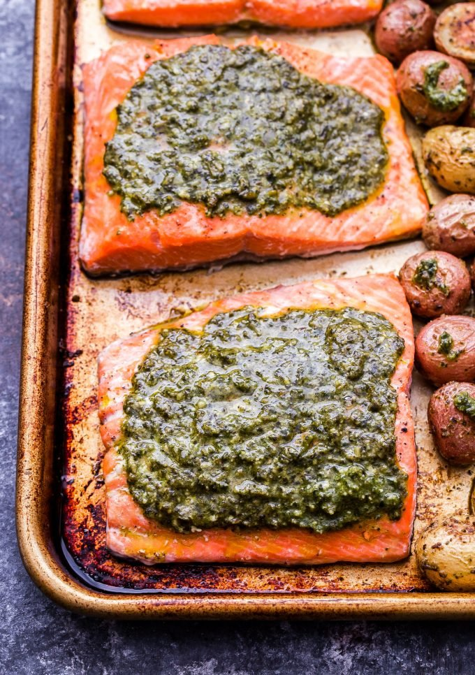 Salmon fillets topped with basil pesto on a sheet pan.