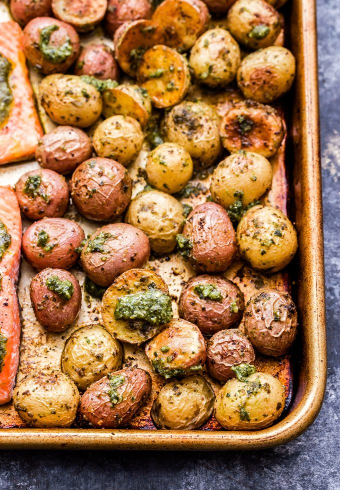 Roasted potatoes covered in pesto on rimmed sheet pan.