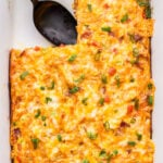 Sweet Potato, Bacon and Egg Breakfast Casserole in white baking dish with a piece cut out.