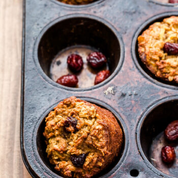 Gluten Free Apple Cinnamon Muffins in muffin pan with dried cranberries.