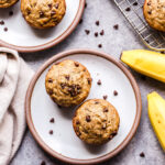 Two Gluten Free Banana Chocolate Chip Muffins on a white plate with a linen napkin and bananas next to the plate.