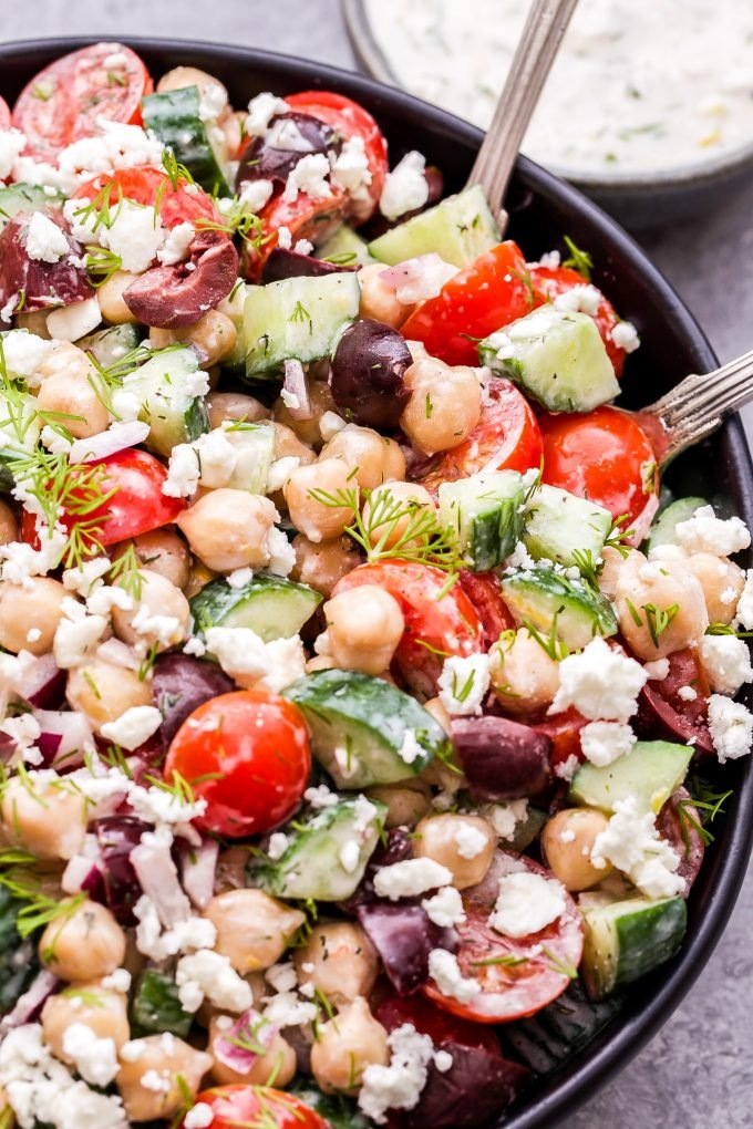 Greek Chickpea Salad with cucumbers, tomatoes, olives and dill tossed in a Tzatziki Dressing in black bowl.