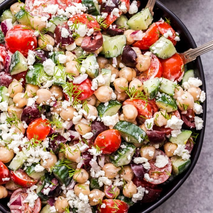 Greek Chickpea Salad with Tzatziki Dressing in black bowl with a small bowl of dressing behind it and serving spoons in the salad.