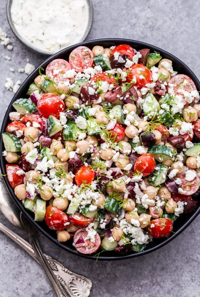 Greek Chickpea Salad with Tzatziki Dressing in black bowl with a small bowl of dressing behind it and serving spoons at the side.