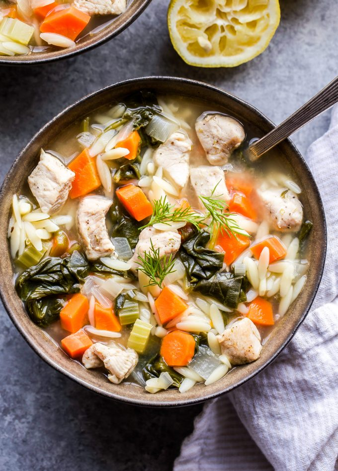 Lemon Chicken, Spinach and Orzo Soup in a bowl with a spoon and lemon half in the background.