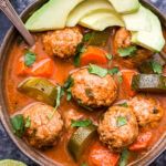 Mexican Meatball Soup in bowl with spoon topped with cilantro and avocado slices.