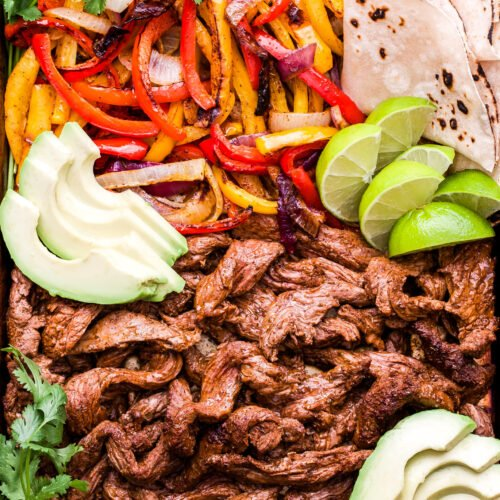 Steak Fajitas on a rimmed sheet pan with tortillas, avocado slices, lime wedges and cilantro