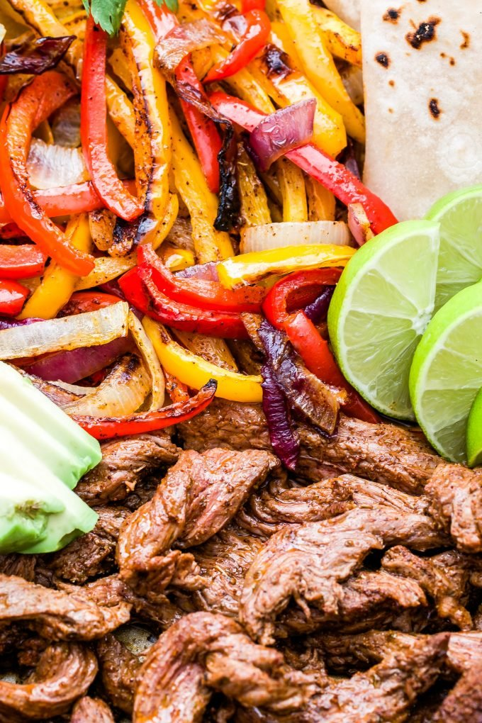 Steak Fajita meat, red and yellow peppers, and onions on a rimmed sheet pan with tortillas, avocado slices, lime wedges and cilantro