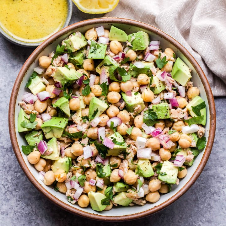 Avocado Chickpea Tuna Salad in round bowl with a small bowl of lemon vinaigrette behind it.