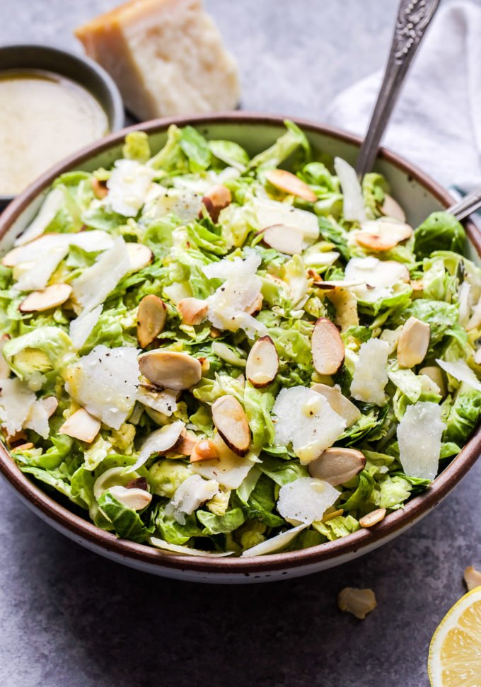 Lemon Parmesan Shaved Brussels Sprouts Salad in serving bowl with lemon vinaigrette behind it and a wedge of parmesan cheese.