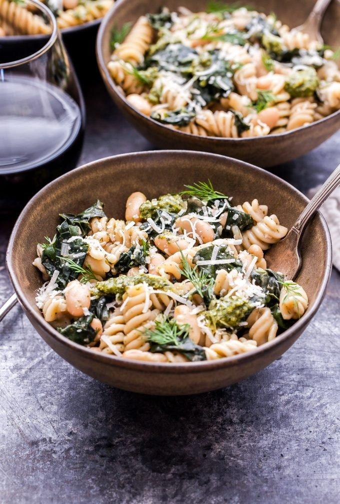 Creamy Kale, White Bean and Pesto Pasta in a brown ceramic bowl with a spoon.