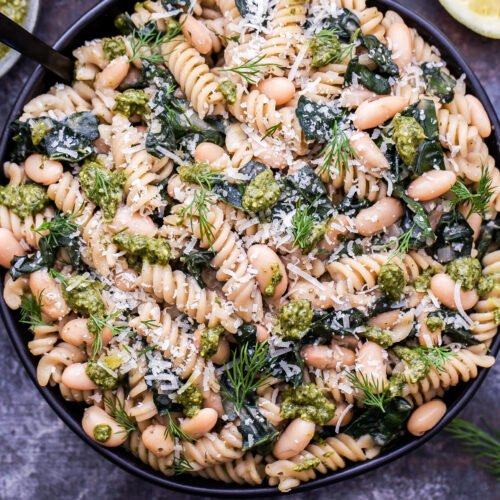 Creamy Kale, White Bean and Pesto Pasta in a black serving bowl with a spoon.