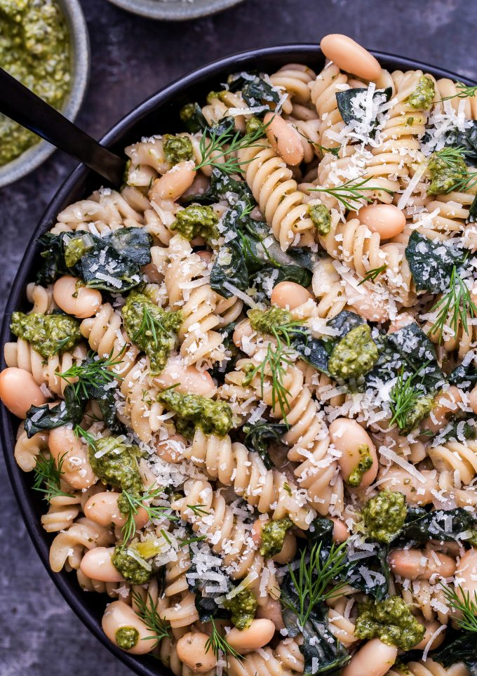 Creamy Kale, White Bean and Pesto Pasta in a serving bowl with a black serving spoon.