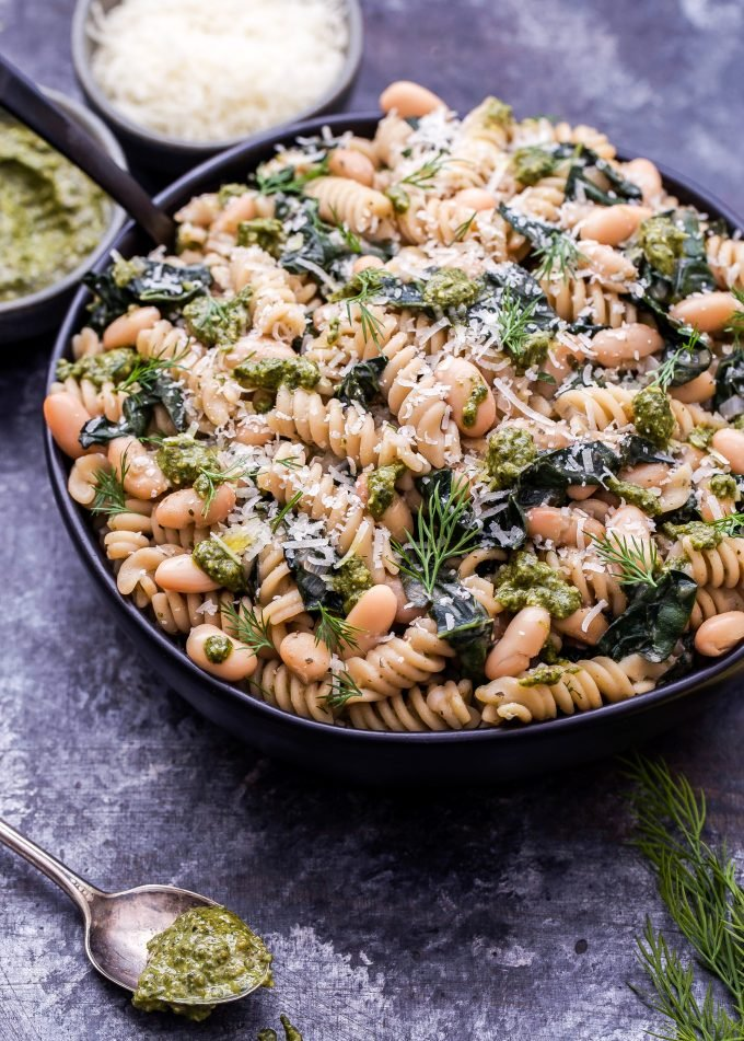Creamy Kale, White Bean and Pesto Pasta in a serving bowl with a spoon of pesto in front of it.