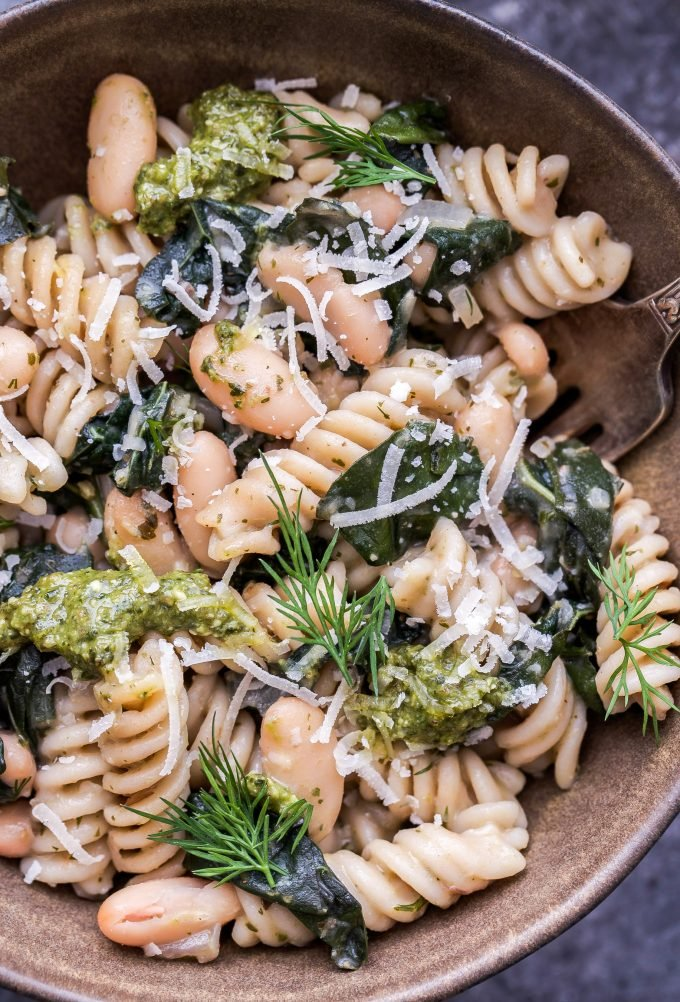Closeup of Creamy Kale, White Bean and Pesto Pasta in a brown ceramic bowl.