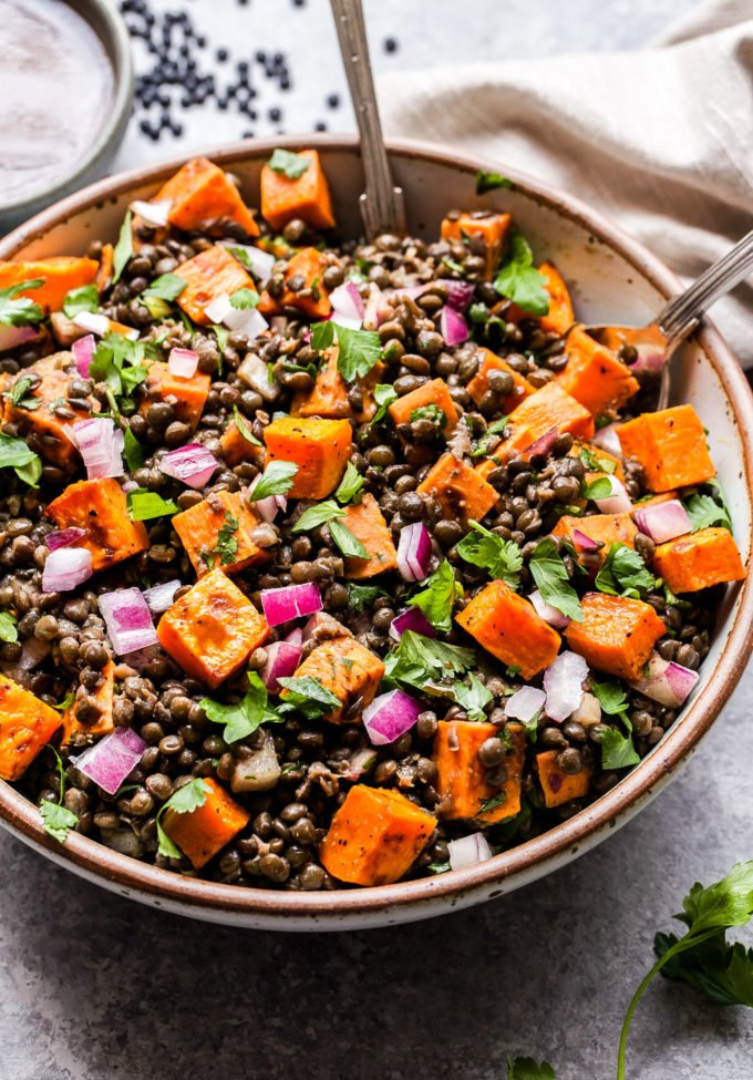 Roasted Sweet Potato Lentil Salad in round serving bowl with serving spoons in the bowl.