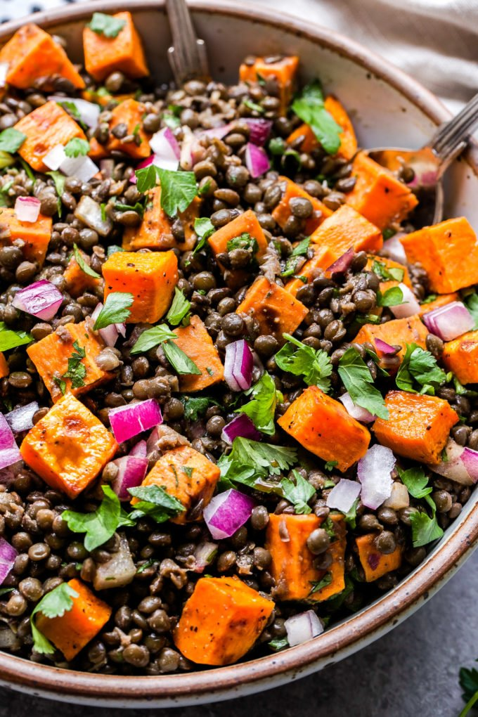 Roasted Sweet Potato Lentil Salad topped with parsley, cilantro and diced red onions.