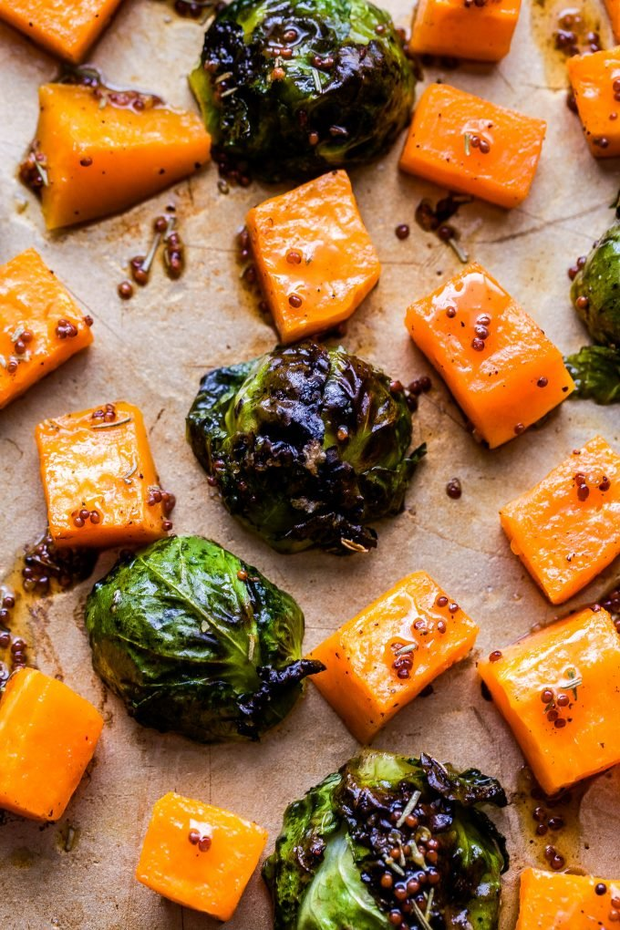 Butternut Squash and Brussels Sprouts on sheet pan covered in maple mustard sauce.