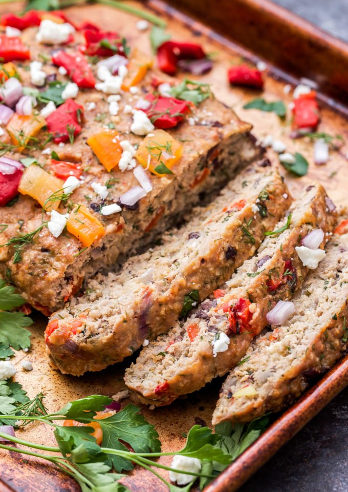 Mediterranean Turkey Meatloaf sliced and topped with roasted red peppers, parsley and feta.