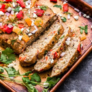 Mediterranean Turkey Meatloaf on a sheet pan topped with roasted red pepper, feta and parsley