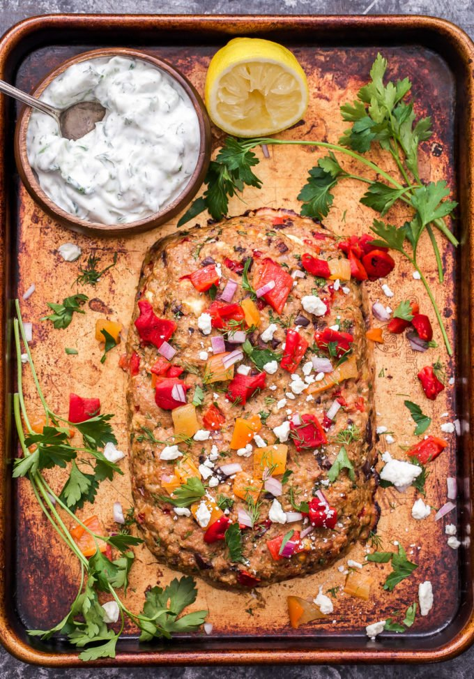 Mediterranean Turkey Meatloaf on a sheet pan with a bowl of tzatziki sauce