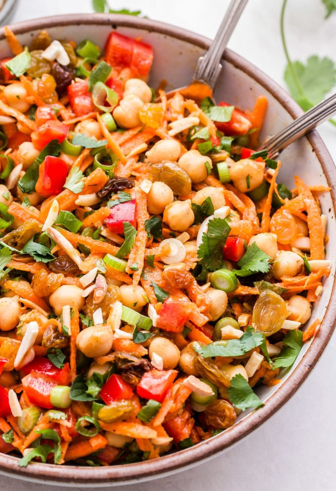 Moroccan Chickpea Salad with carrots, red bell pepper, golden raisins, almonds, cilantro and mint. In white serving bowl with spoons.