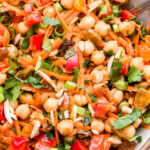 Closeup photo Moroccan Chickpea Salad with carrots, red bell pepper, golden raisins, almonds, cilantro and mint.
