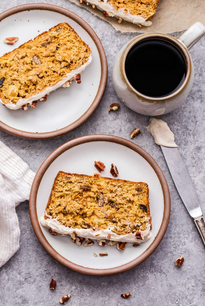 Overhead photo of Oatmeal Carrot Cake Bread slices on two white round plates with a mug of coffee next to them.