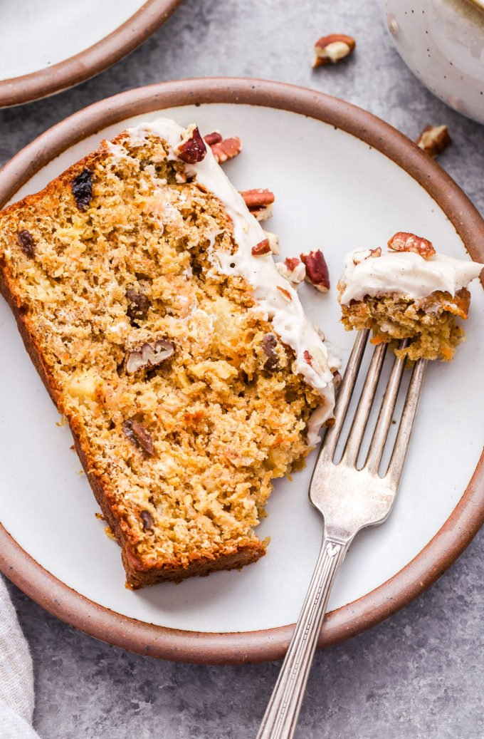 Slice of Oatmeal Carrot Cake Bread on white plate with a piece broken off and on a fork