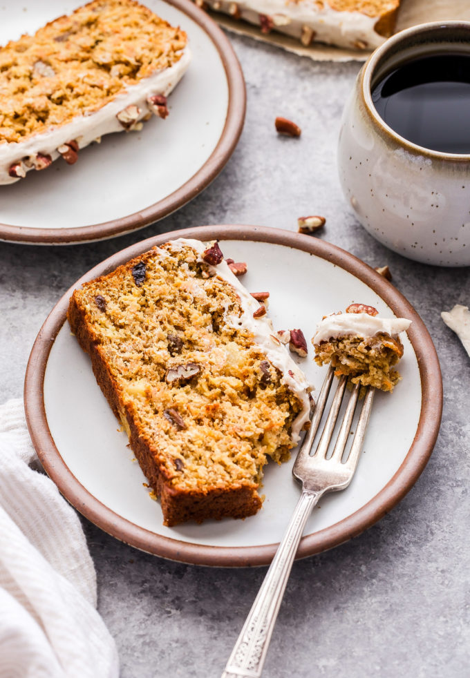 Slice of Oatmeal Carrot Cake Bread on white plate with a piece broken off and on a fork. Coffee and a second plate with a slice behind it.