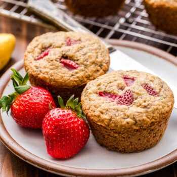 Two Strawberry Banana Muffins on a round white plate with a butter knife and two strawberries.