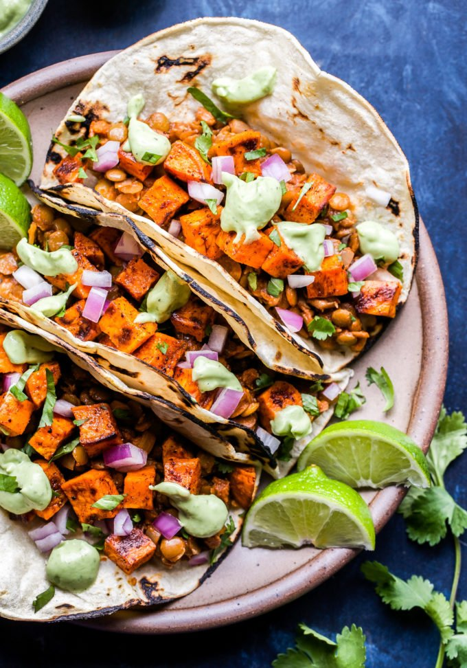 Three Sweet Potato and Lentil Tacos on a round plate with lime wedges. Tacos are topped with avocado cream.