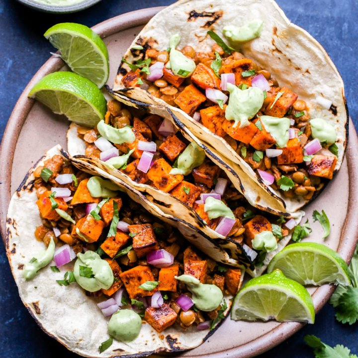Overhead photo of Sweet Potato and Lentil Tacos topped with avocado cream on a round plate and small bowl of avocado cream behind them.