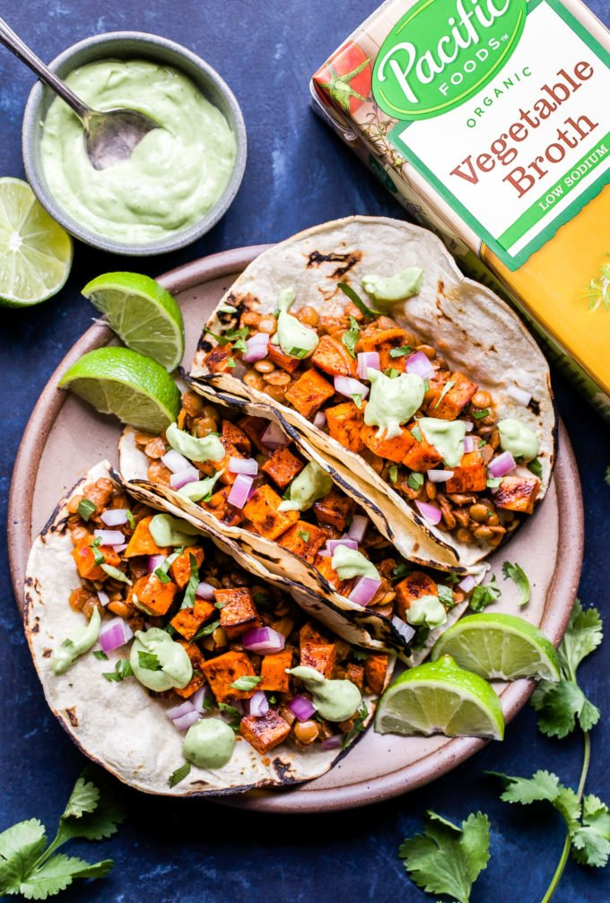 Three Sweet Potato and Lentil Tacos on a plate with a bowl of avocado cream beside them and a box of vegetable broth in the background.