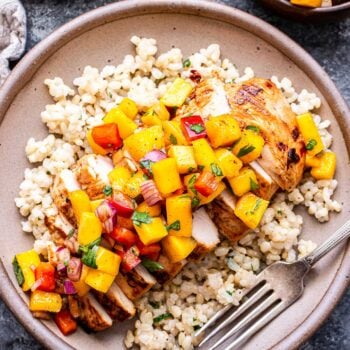 Overhead photo of a plate with rice and a chipotle lime grilled chicken breast topped with mango salsa.