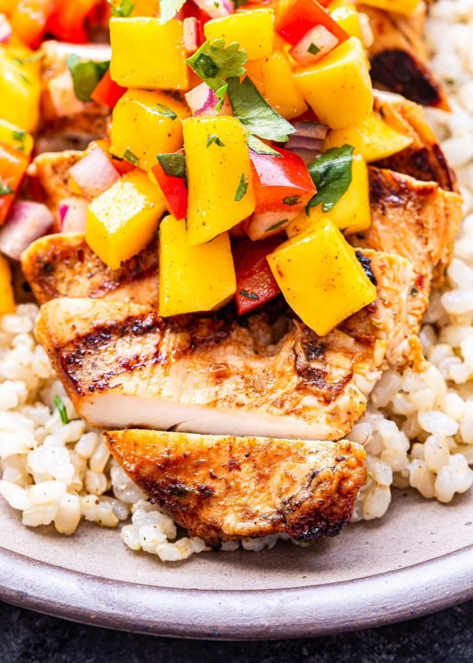 closeup photo of a Chipotle Lime Grilled Chicken breast on top of rice topped with mango salsa.